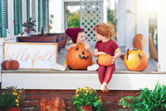 Boy and girl enjoying decorating pumpkins with fall decor.