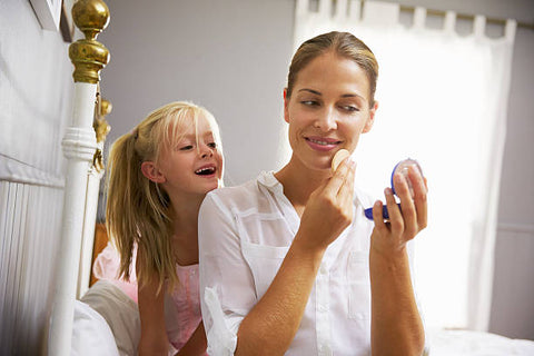 Female child watching mother put on makeup