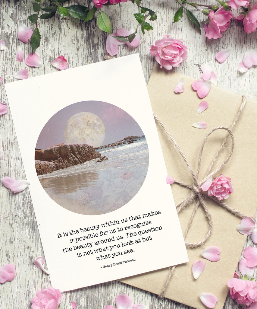 Moon art postcard with a quote from Henry David Thoreau next to a brown envelope and sprinkles of rose petals and flowers.