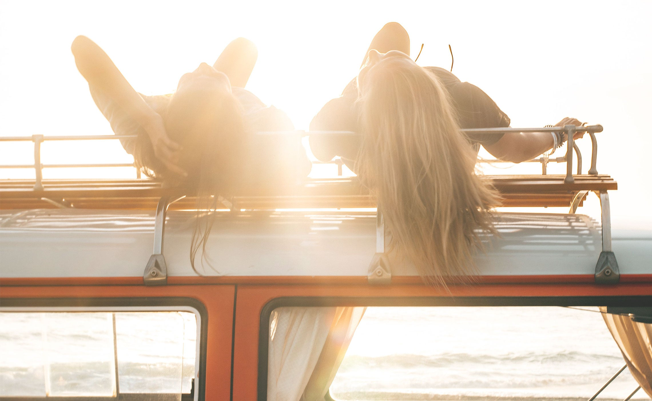 Two friends laying on top of a camper van roof watching the sunset over the ocean.