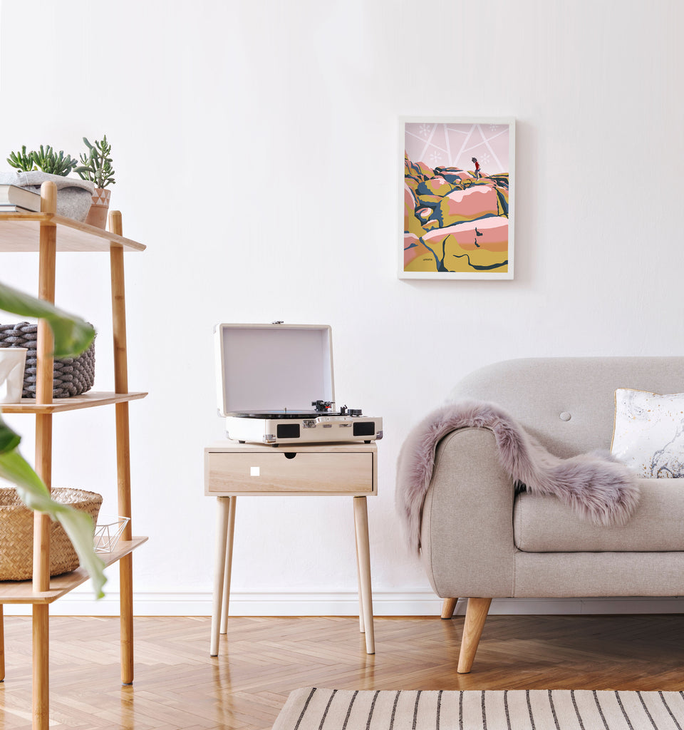 Minimal mid century modern style apartment living room with framed boho beach artwork on wall.