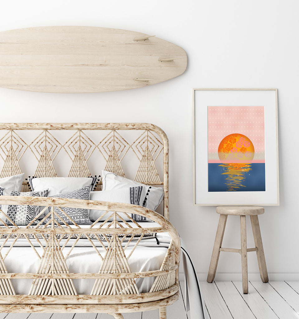 Coastal bedroom with a blush pink and orange 70s style ocean sunset poster.