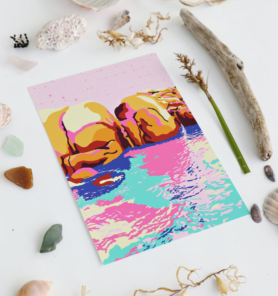 Beach inspired flatlay showing an A4 bright colourful seascape drawing next to seashells and driftwood.