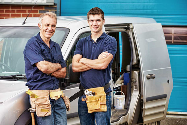 two tradies next to a van with tools