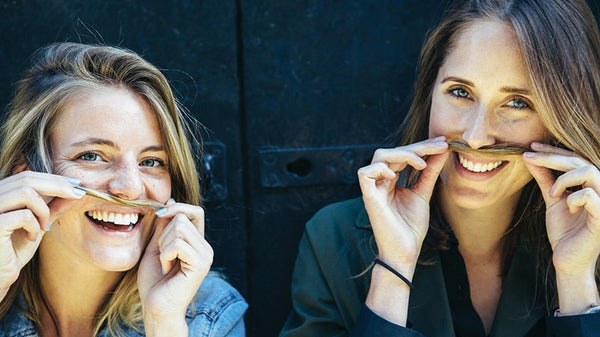 two women with fake mustaches