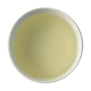 A face-down picture of steeped Long Jing. The steeped tea is a soft, light green-yellow color.