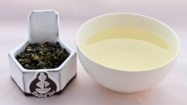 Ali Shan tea leaves on the left, tightly rolled into finger nail sized balls. On the right is cup with pale yellow tea from steeping the leaves.
