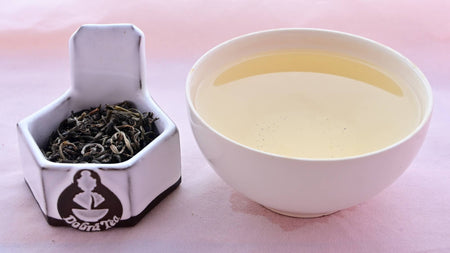 A side-by-side comparison of Ancient Arbor (Ha Giang Che Xanh) leaves and steeped tea. On the left, the leaves are curled around nearly into circles. They are dark green with the occasional light green tossed in. On the right, the steeped tea is a pale yellow.