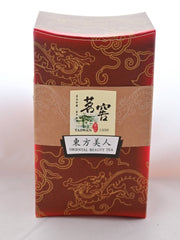 "The Bai Hao box is dark red, with golden designs of dragons twisting over it. In the middle is a golden band, with text that reads ""Taiwan, 1936. Oriental Beauty Tea."" There are Chinese letters above each of the English translations."