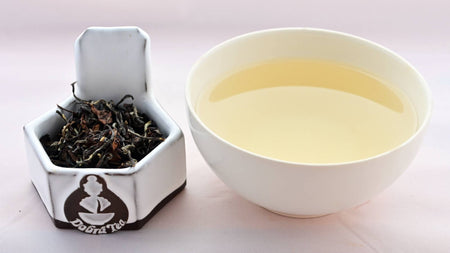 Crisp and curly tea leaves, rolled into long twisting shapes range from brown to pale green on the left. On the right, a cup of steeped Bai Hao tea is a pale peach color.