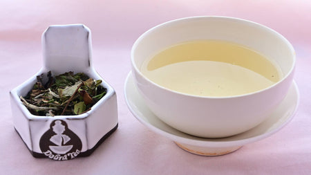 A side-by-side comparison of Bai Mu Dan leaves and steeped tea. On the left, the leaves are flat and large, and have a green tint. On the right, the steeped tea is a pale yellow.