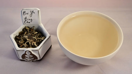 Bai Ya Bing Cha tea leaves on the left, steeped tea on the right. The steeped tea has a pale peach color.