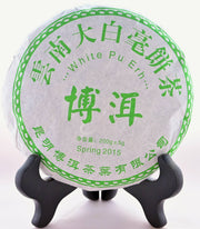 "A Bai Ya Bing Cha tea disk shits on a black book holder. Chinese lettering in bright green runs around the package. The English translations are written underneath. ""White Pu Ehr. Spring 2015. 200 grams."""
