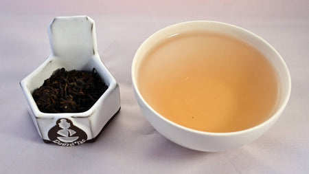 A side-by-side comparison of Bamboo Pu'er leaves and tea. The leaves on the left are dark grown and shadowy. The tea on the right is a warm red-brown.