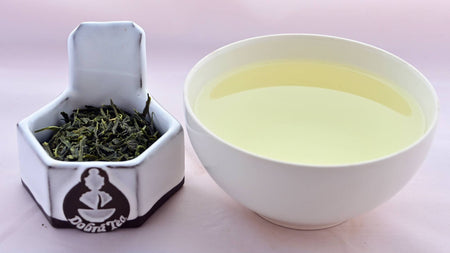 A side-by-side comparison of Bancha leaves and the steeped tea. On the left, the leaves appear dark green and thin. On the right, the steeped tea is a soft yellow.