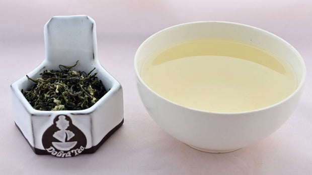 A side-by-side comparison of Bi Lou Chun leaves and steeped tea. On the left, the leaves range from bright green to dark green. They are twisted and curling, and appear slightly fuzzy. On the right, the steeped tea is a pale yellow color.