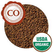 A close-up of CTC tea pellets, which are small, round, and uniform. They are all a light brown color. They have Certified Organic and USDA Organic certifications.
