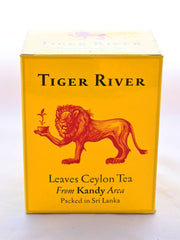 "The Ceylon Tiger River box is orange with a red lion holding a flowering tea cup drawn in the center. English lettering reads: ""Tiger River. Leaves Ceylon Tea. From Kandy Area. Packed in Sri Lanka."""