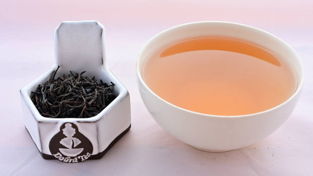 A side-by-side comparison of Ceylon Tiger River leaves and steeped tea. On the left, the leaves are a black color, and resemble small twigs. On the right, the steeped tea has a brown-red color.