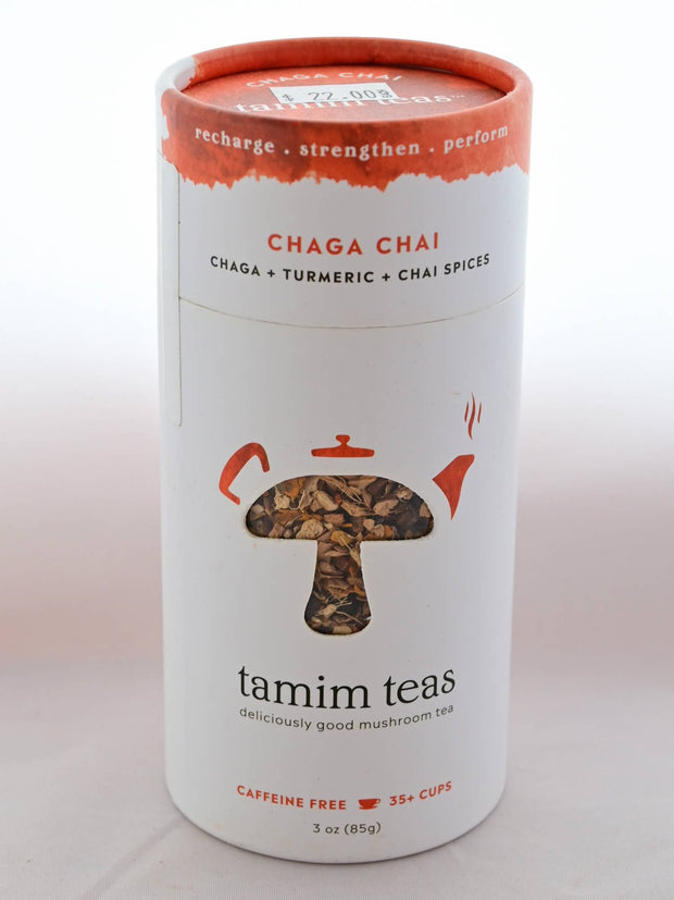 "The Chaga Chai tin is cylindrical and mostly white with a splash of orange on top. In the middle, a clear cutout in the shape of a mushroom shows part of the blend, with orange tea pot decorations around the mushroom's crown. Text reads: ""Recharge. Strengthen. Perform. Chaga Chai. Chaga and tumeric and chai spices. tamim teas. deliciously good mushroom tea. Caffeine free. 35+ cups. 3 oz (85 grams)."""