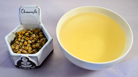 A side-by-side comparison of dried chamomile buds and steeped tea. On the left, the dried buds are about the size of your smallest finger nail and are pale yellow in color. On the right, the steeped liquid is the exact color of the chamomile buds.