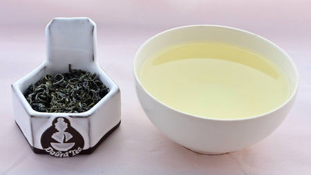 A side-by-side comparison of Che Xhan leaves and steeped tea. On the left, the leaves are a rich, dark green, and curl quite tightly while never fully rolling. On the right, the steeped liquid is a pale green.
