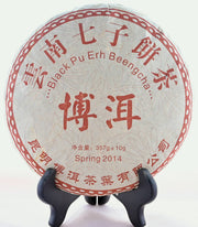 "A Chi Tse Bing Cha disk is shown on a black book stand. The disk is wrapped in a white tissue paper decorated in red. Chinese letters circle the outside, with English translations underneath: ""Black Pu Erh Beengcha. Spring 2014. 357 grams."""