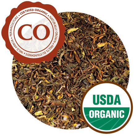 A close-up of Darjeeling Himalaya leaves. They are loosely curled, looking more pressed than previous iterations, and range in color from bright yellow to dark brown. The tea is labeled as Certified Organic and carries a USDA Organic label.
