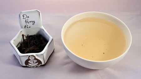A side-by-side comparison of Da Hong Pao leaves and steeped tea. On the left, the leaves are dark brown and loosely curled. On the right, the steeped tea is a soft peach.