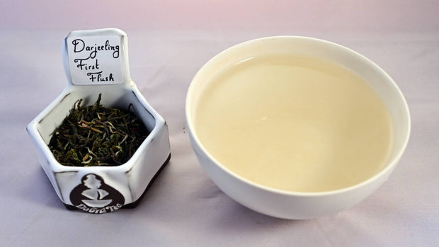 A side-by-side comparison of Darjeeling First Flush leaves and tea. On the left, the leaves are loosely curled and range in color from dark green to pale green. On the right, the steeped tea is a pale yellow.