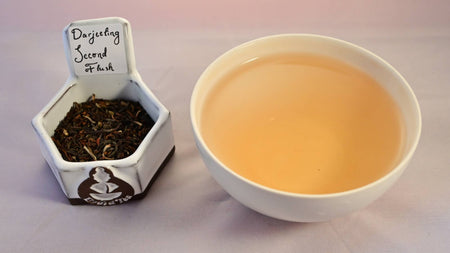 A side-by-side comparison of Darjeeling Second Flush leaves and steeped tea. On the left, the leaves are dark brown with spots of pale green. On the right, the steeped tea is a pale orange color.