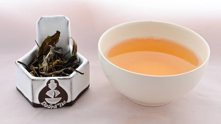 A side-by-side comparison of Dhara leaves and steeped tea. On the left, the leaves are tall, broad, and range in color from pale green to bright green. There are a few twig branches mixed among the leaves. On the right, the steeped liquid is a caramel color.