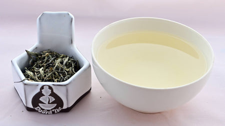 A side by side comparison of Dian Lu Wenshan leaves and steeped tea. On the left, the tea leaves are predominantly pale green and twisted into zig-zaging rolls. On the right, the steeped tea is a pale yellow.