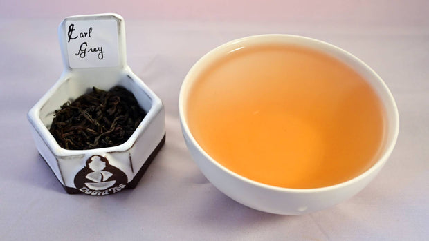 A side-by-side comparison of Earl Grey leaves and steeped tea. On the left, the leaves are black and spiraled loosely. On the right, the steeped tea is a ruddy orange.