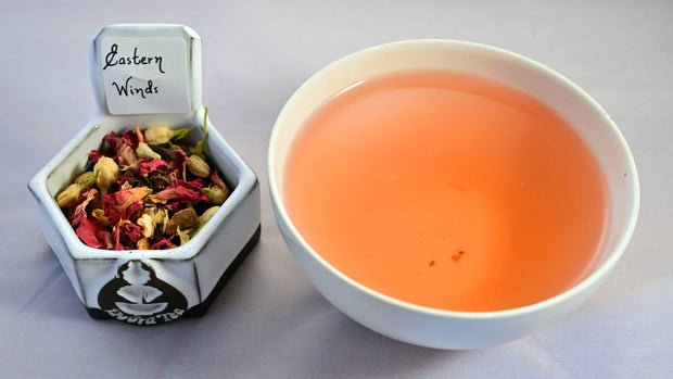A side-by-side comparison of the Eastern Winds herbal blend and steeped tisane. On the left, the tea mixture prominently features hibiscus leaves and dried jasmine buds. On the right, the steeped tisane is dark orange.