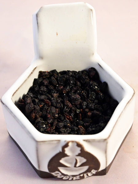 A close-up of dried elder berries. They are black with red undertones, and resemble raisins.