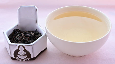 A side-by-side comparison of Feng Huang Dan Cong leaves and steeped tea. On the left, the leaves are dark brown and withered, drooping like dog's ears. On the right, the steeped tea is a dull yellow.