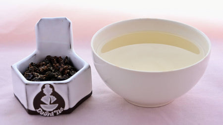 A side-by-side comparison of Gui Fei leaves and steeped tea. On the left, the leaves are small and have been rolled into crumpled, dark pellets. On the right, the steeped tea is a pale yellow.