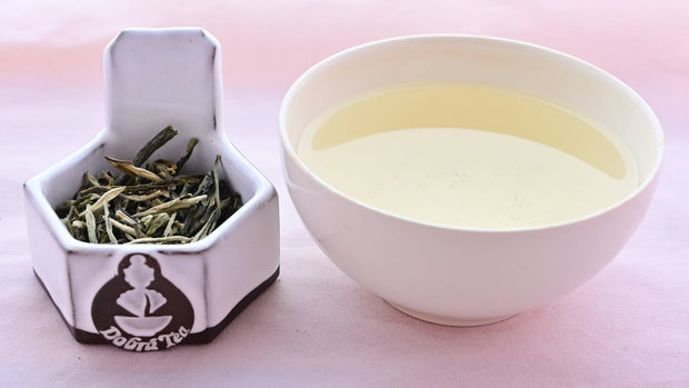 A side-by-side comparison of Huang Ya leaves and steeped tea. On the left, the leaves are long and thick, resembling dried yellow buds more than traditional leaves. On the right, the steeped tea is a pale yellow.