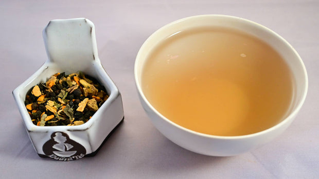 A side-by-side comparison of Immunitea blend and steeped tisane. On the left, the tea blend prominently features elderberries, turmeric, and ginger. On the right, the steeped tisane is a smoky, muted orange.