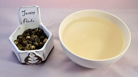 A bowl of rolled leaves next to a cup of prepared tea. The leaves are rolled into tight balls showing patches of light and dark color. The tea is pale yellow.