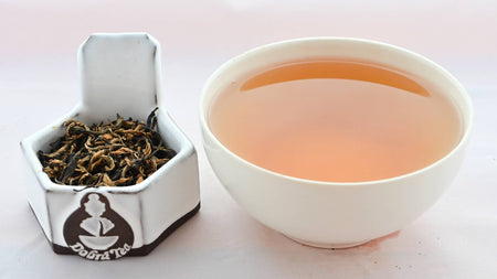 A side-by-side comparison of Jin Zhen leaves and steeped tea. On the left, the leaves are an equal mixture of dark brown and black, and spiral around one another. On the right, the steeped tea is dark orange.