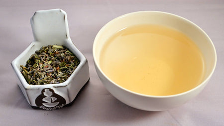 A side-by-side comparison of the Jovialitea blend and steeped tisane. On the left, the blend prominently features lavender and tulsi. On the right, the steeped tisane is a rich yellow color.