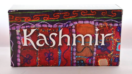 "The paper Taste of Kashmir box features intricate designs and decorations, as though someone hand-embriodered a red and brown blanket with orange, green, purple, blue and other threads. White text reads: ""Kashmir."""