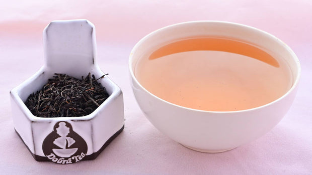 A side-by-side comparison of Kenyan FOP leaves and steeped tea. On the left, the leaves are small, black, and tightly curled. On the right, the steeped tea is a rich orange color.