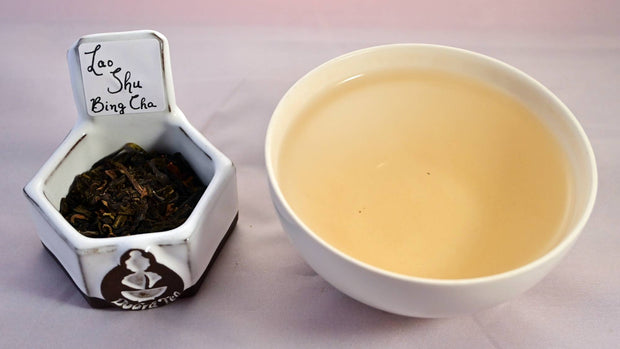A side-by-side comparison of Lao Shu Bing Cha leaves and steeped tea. On the left, the leaves are dark brown to black, and flaky. On the right, the liquid is a pale peach color.
