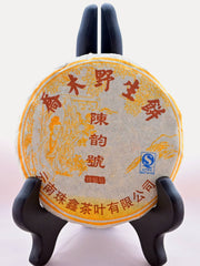 The Lao Shu Bing Cha disk is fully wrapped and displayed on a black book holder. The tissue paper cover is white, with yellow designs of a tree and someone looking at flowers on it. Red Chinese lettering circles the top, middle, and bottom. There is a blue stamp in the right-center.