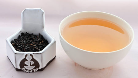 A side-by-side comparison of Lapsang Souchong leaves and steeped tea. On the left, the tea leaves are black and fit snugly together. On the right, the steeped tea liquid is pale orange.