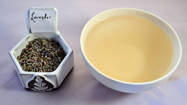 A side-by-side comparison of dried lavender buds and steeped tea. On the left, the dried lavender buds are a faint periwinkle. On the right, the steeped liquid is pale yellow.