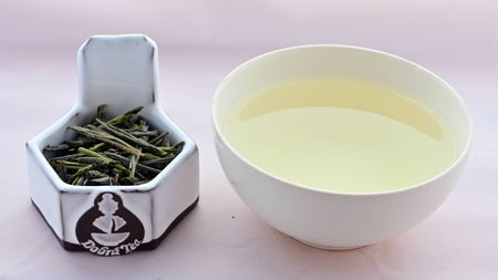 A side-by-side comparison of Lui'An Gaupian leaves and steeped tea. On the left, the leaves are long and narrow, and only barely curled into loose tubes. On the right, the steeped liquid is pale yellow.